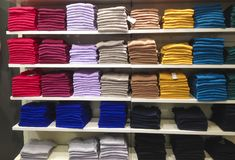 Rows of folded clothes. Rows of folded colorful clothes in a shop Royalty Free Stock Photos