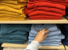 Rows of folded colorful pullover in a shop. Rows of folded colorful clothes in a shop royalty free stock photos
