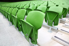 Rows of folded, green seats in empty stadium. Stock Photography