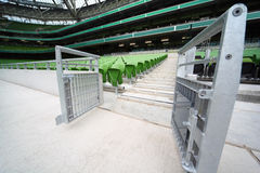 Rows of folded, green seats in empty stadium Stock Images
