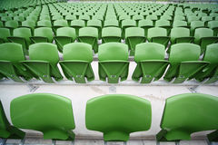 Rows of folded, green seats in empty stadium. Royalty Free Stock Image