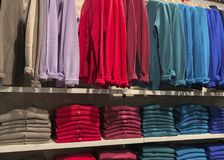 Rows of folded clothes. Rows of folded and hanging colorful clothes in a shop Royalty Free Stock Photography