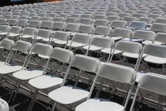 Rows of folding white chairs Stock Images