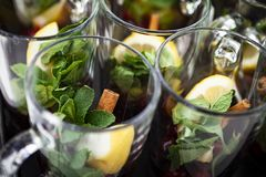 Rows of glasses with lemon crushed cinnamon and dog rose. Fresh herbal tea. stock photos