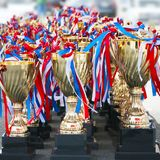 Rows of Golden Trophy Cups with Red, White and Blue Stripes Attached.  royalty free stock photo