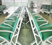 Rows of green chairs for passengers. Waiting zone area with rows of green chairs in opposite direction. Use in concepts of seats for passengers at airport royalty free stock image
