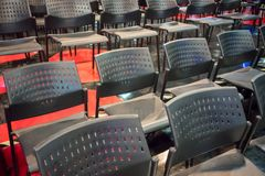 Rows of grey plastic chair with stainless steel metal legs arranged on shiny floor in hall. stock photos