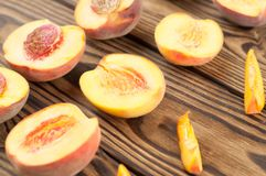 Rows of halves of peach and slices of peach. On rustic old wooden planks stock photo