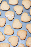Rows of heart shaped biscuits on metal baking tray Royalty Free Stock Photos
