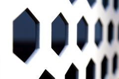 Rows of hexagonal shaped holes on a white metal board Stock Photos