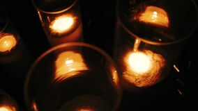 Rows of hundreds burning votive candles in dark moody sacral environment, background texture