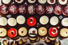 Rows of italian mignon cakes on a glass stand. Rows of coloured italian mignon cakes on a glass stand royalty free stock photos