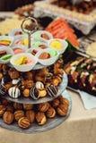 Rows of italian mignon cakes on a glass stand. Rows of coloured italian mignon cakes on a glass stand stock photos
