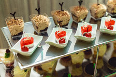 Rows of italian mignon cakes on a metal stand stock images