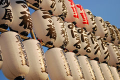 Rows of Japanese paper lanterns at sunset. Rows of traditional Japanese paper lanterns hung neatly on bamboo sticks, bathed in warm sunset light Royalty Free Stock Photo