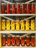 Rows of jars of pickled peppers and lemons are on the rack Stock Photos
