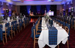 Laid dinner tables at formal event. Rows of laid dinner table at formal event with stage in background Stock Photos