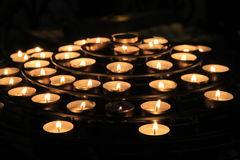 Rows of lit candles, casting soft shadows in room of prayer Stock Photo