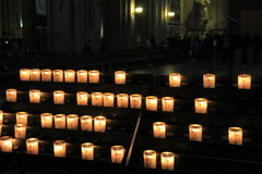Rows of lit prayer candles in dark church Royalty Free Stock Photo