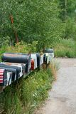 Rows of Mail Boxes sits becide a Mountian Pass Road stock photo