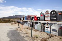 Rows of mailboxes in desert with mountains in background Royalty Free Stock Images
