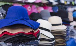 Rows of multi-colored straw hats for sale on shelves in a market Stock Images