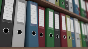 Rows of multicolored binders on shelves close up shot, shallow focus, CGI. Rows of multicolored binders close up shot Royalty Free Stock Images