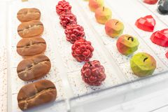 Rows of multicolored cakes and desserts in the window of a pastry shop. Modern mousse dessert, sweet snack. in the form. Rows of multicolored cakes and desserts stock photography