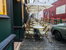 Rows of neatly arranged cafe tables and umbrellas waiting for diners, Paris, France. Paris, France, 2016: Rows of cafe tables line both sides of a cobblestone Stock Image