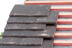 Rows of new roof tiles being fitted to wooden battens Royalty Free Stock Photos