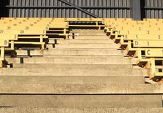 Rows of numbered old-fashioned grandstand seating divided by ais Royalty Free Stock Photo