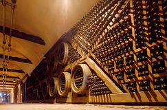 Rows of oak barrels and bottles inside huge cellar Khareba Winery with cold underground tunnel Royalty Free Stock Photography