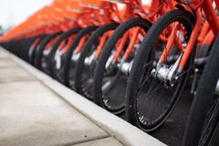 Rows of orange bikes parked next to each other stock image