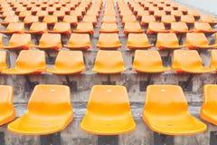 Rows of orange plastic stadium seats Stock Photography