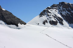 Rows of people over the snow of the Swiss Jungfrau Royalty Free Stock Photography
