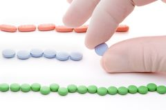 Rows of pills. Three rows of red green and blue pills and hand picking blue one royalty free stock images