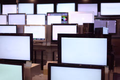 Rows of plasma TVs stand on shelves Royalty Free Stock Photos