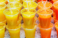 Rows of plastic cups with fruit juices Stock Image