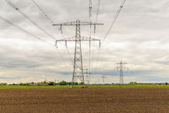 Rows of power pylons in a rural landscape Royalty Free Stock Photo