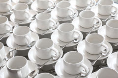 Rows of pure cup and saucer with teaspoon. Many rows of pure white cup and saucer with teaspoon, reflection on table Royalty Free Stock Photography