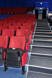 Rows of red and blue seats, entrance and stairs in auditorium Stock Image