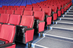 Rows of red and blue seats and stairs in auditorium Royalty Free Stock Images