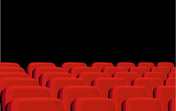 Rows of red cinema seats on a black background. Stock Image