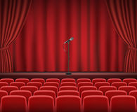 Rows of red cinema or theater seats in front of show stage Stock Images