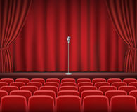 Rows of red cinema or theater seats with microphone. A Rows of red cinema or theater seats with microphone Stock Photo