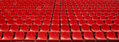 Rows of red football stadium seats with numbers. Royalty Free Stock Image