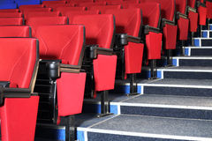 Rows of red seats and grey stairs in auditorium Stock Images