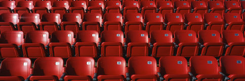 Rows of red stadium seats. These are bright red outdoor stadium seats with seats that fold up. They are located at a baseball stadium royalty free stock photography