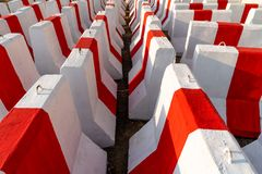 Rows of red and white concrete barriers waiting to be used in traffic control and safety. 2 royalty free stock image