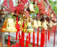 Rows of red wind bells golden buddhist prosperity bell at chinese temple people wish and hang them.  stock photo